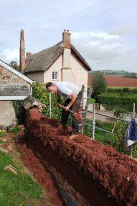 John Tandy repairing a cob wall